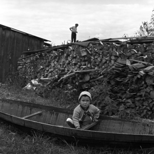 "Ilya. The grandson of Peter Milimov, playing in the yard in the ""oblasok"" canoe, boat made of a single piece of wood and used by local people for fishing. Noviy Vasyugan. Tomsk region. Russia. 2009."