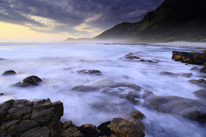 Motion / A seascape of the rugged coast on the Atlantic Ocean, along the Cape Peninsula, South Africa. A double long exposure with rocks and blurred waves in the foreground and mountains and cloudy sky at sunset in the background.