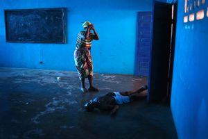 """Blue Room. Omu Fahnbulleh stands over her husband Ibrahim after he fell and died in a classroom used for Ebola patients. From the series """"Ebola Crisis Overwhelms Liberian Capital."""" Winner of L'Iris d'Or, 2015 Sony World Photography Awards."""