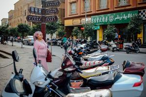 A Uighur woman waits for someone  in old Kashgar, Xinjiang Uighur Autonomous Region, China.