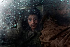A young boy looks from a car stopped at an Afghan National Army checkpoint in the Korengal Valley, Afghanistan, on April 2, 2009. © Adam Ferguson