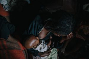 Tesfa sits on the edge of her bed and breast feeds her youngest child. Tesfa became blind at a young age and struggles to support three of her four children. The other she was forced to send to an orphanage.