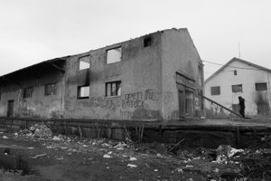 A migrant enters the abandoned train depot he is living in.