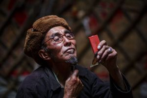 A Kyrgyz man trimming his beard, living in a traditional yurt in the upper wakhan.
