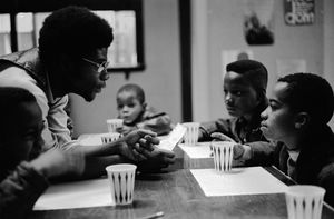 """November, 1970 - Chicago, Illinois, USA: Free Breakfast Program.  Panther Jerry Dunigan, known as """"Odinka"""", talks to kids while they eat breakfast on Chicago's south side. The Free Breakfast for School Children Program was a community service program run by the Black Panther Party."""
