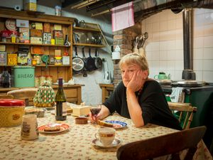 Jenny's listening yet not impressed, in her kitchen
