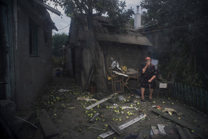 A Luhansk citizen sits outside her destroyed house