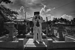 """Mister Matsumoto, Yakuza member and TEPCO contractor is praying on his family grave, from the series Fukushima """"No Go"""" Zone, © Pierpaolo Mittica."""