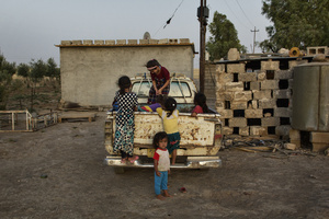 A group of displaced children play on the back of a pick up truck at the chicken farm of Dibaga. 47 families, 260 people, girls, boys, men and women from Jarallah now live together in one building. 04/07/2015.