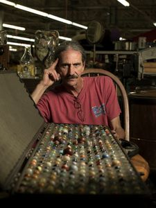 Richard Crowell sells antiques in the Clayton Indoor Flea Market in Clayton, GA. He's pictured here with his collection of vintage and rare marbles. © Forest McMullin