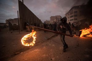 A Palestinian youth throws a burning tire during clashes with Israeli police at the Palestinian refugee camp of Shuafat in East Jerusalem, November 5, 2014.