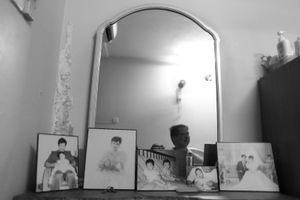 © Nafise Motlaq -A collection of old photos of Lee and his family located in front of mirror at his bedroom..