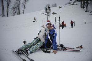 A sweet couple kiss on the snow slopes of Rosa Khutor ski resort.