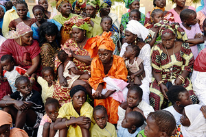 The women and children from the Senegalese village Soune have assembled to watch the men fighting in a wrestling match on April 20, 2012. The wrestling matches in the country are delivered occasionally at village celebrations to entertain the audience.