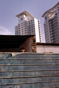 Man walks under corrugated makeshift housing against a backdrop of new luxury flats.  Xi'an, China. 22 December 2006