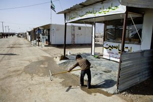 A boy cleaning the front entrance of his family's shop in Zaatari's main road.© Tom Verbruggen