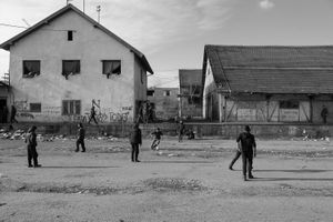 A group of migrants is playing soccer in front of their temporary home.