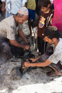 Yemeni fishers remove the ink from squid at Mocha port.