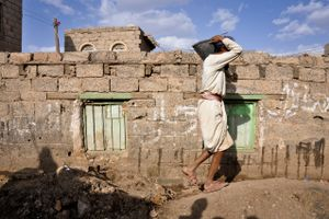 A worker belonging to the caste carries a bucket of sand through a building site in Sana'a.