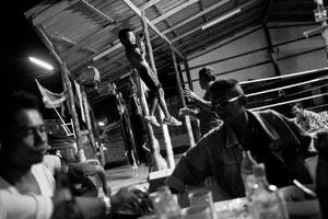 A boy is making exercise. In the front the trainer is drinking whiskey with his friends and the father. © Sandra Hoyn
