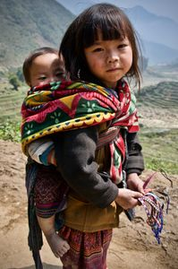 Young H'mong girl with a baby in the rice terraces near Ta'van village selling bracelets to tourists trekking in the region.