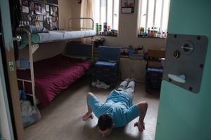 An 'enhanced' prisoner doing press ups in his room on H wing at the Young Offenders Institution  in Aylesbury, United Kingdom.  Under the Incentives and Earned Privilege Scheme, prisoners in the U.K. can earn extra privileges for good behaviour such as wearing their own clothes, having televisions in their cells, and having more free time to socialise.