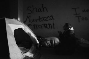 A refugee is performing a night time prayer inside the room he is sharing with seven other people. To have a minimum of privacy some migrants use tents as their home.