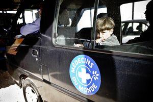 A boy in a Médecins du Monde car. © Tom Verbruggen