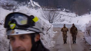 Farindola, Italy (2017). Avalanche Hotel. Rescuers, a fireman and two soldiers, walk away from the Rigopiano hotel, on the day the last bodies were recovered. The remains of the luxury resort are visible behind them, on the top of the frame.