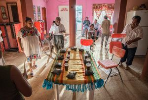 After the praying is done and the ancestors have had their part of the offerings everybody sits down to eat,