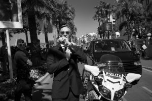 """a security agent liaises with a collegue using his wrist radio while the stars of """"The Expendables 3"""" greet the crowds on the Croisette, 2014  © Alison McCauley"""