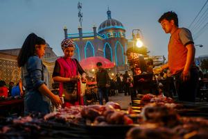 Uighur women buy a street food at the night market in old Kashgar, Xinjiang Uighur Autonomous Region, China.