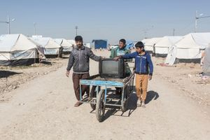 22/01/2015 -- Kirkuk, Iraq -- Three young displaced Iraqi kids bring a TV they have just purchased to their tent in Laylan camp, south of Kirkuk.