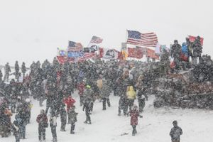 Protestors gather in prayer after marching toward barricades on the Backwater Bridge on Highway 1806 with support from US military veterans on Army Corps of Engineers land bordering the Standing Rock Indian Reservation in Cannon Ball, North Dakota in December 2016.