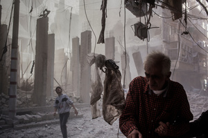 A blasted neighbourhood 10 minutes after a helicopter rocket. The young boy looks up at an apartment in flames while an old man helps his wife seeking shelter.