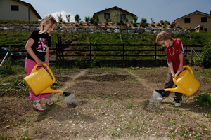 Enfants dans le jardin scolaire dans un nouveau quartier de villas. Kids gardening in a new neighborhood