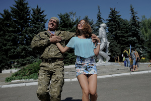 Ukrainian soldier dancing with a local girl at the festival, organized by farmers to celebrate the Independence Day of Ukraine. Novoselivka, Donetsk region, 20 km from Donetsk. August 23, 2015.