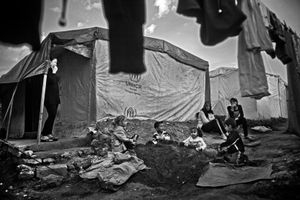 Though they have limited space inside the tent, Children always prefer to play outside on the ground and with sand. They are trying to build their little home by the sand. Their mothers are also watching that play of hope. © Khaled Hasan
