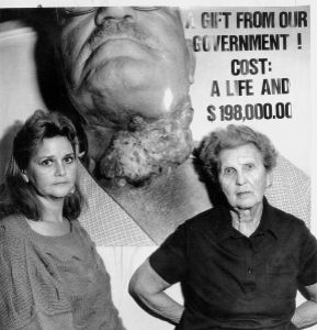 Test Site worker Bonnie Lee Daniels and her mother Marjorie Lease stand before a photo they took of father/husband, test site worker Hap Lease, as he lay dying of esophageal cancer.  Las Vegas, Nevada, 1986