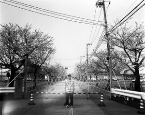 """Mr. Sanbe used to live right outside of the exclusion zone. He came to visit to see the cherry blossoms near his old house. From the series """"Fragments/Fukushima"""" © Kosuke Okahara"""