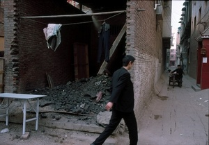 Man walks by makeshift toilets in back streets. Xi'an, China. 22 December 2006