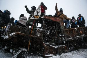 Protestors stand on an abandoned and burned vehicle on Highway 1806 during an action against the Dakota Access Pipeline in Cannon Ball, North Dakota in December 2016.