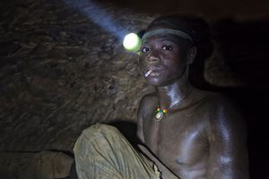 "His ""office"" is a 50m deep, narrow, dangerous and claustrophobic pit. The air is thick, hot and humid, with constant dust that turns his dark arms and face white. He wears a flashlight strapped to his head as he chips ore from the walls into a spece he can barely sit up in. You can barely breathe down here, but for a break, Yakuba lights a cigarette. © Matjaz Krivic"