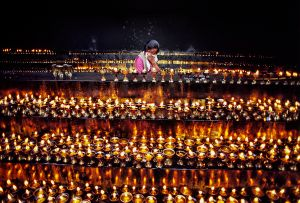Lhasa, Tibet: A girl in front of the famous Jokhang temple is carefully filling the candles with yak oil, for they should never die out. © Matjaz Krivic
