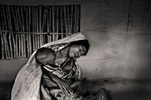 A mother grieves as her child lapses into unconsciousness. The tumour on her child's back has worsened. Her husband is fishing and will not return that day. Chuna, Satkhira. © Munem Wasif/VU'
