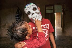 Kids play with a Day-of-the-Dead mask they purchased in a store.