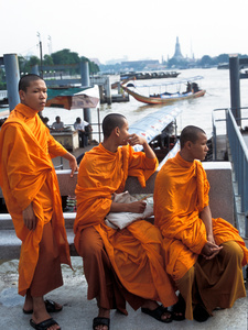 Young buddhist monks waiting for a ferry boat