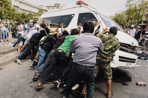 Anti-government protesters overturn an ambulance following clashes between demonstrators and police.