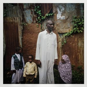 A Somali refugee family stand next to their corrugated iron house in Kibera. The Kibera slum is the largest slum in Nairobi with around half a million inhabitants.