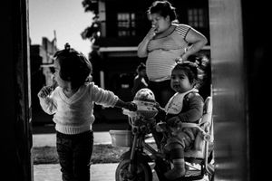 Stefi smokes a cigarette on the street in Monte Chingolo, while Maite and Mia play together. © Sarah Pabst